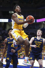 Pittsburgh's Xavier Johnson, center, shoots between Sean McNeil (22) and Miles McBride (4) during the first half of an NCAA college basketball game, Friday, Nov. 15, 2019, in Pittsburgh. (AP Photo/Keith Srakocic)