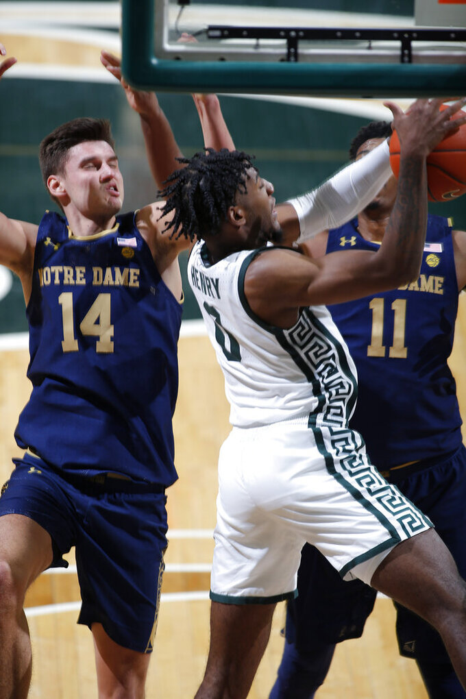 Michigan State's Aaron Henry, center, and Notre Dame's Nate Laszewski, left, and Juwan Durham, right, vie for a rebound during the second half of an NCAA college basketball game Saturday, Nov. 28, 2020, in East Lansing, Mich. Michigan State won 80-70. (AP Photo/Al Goldis)
