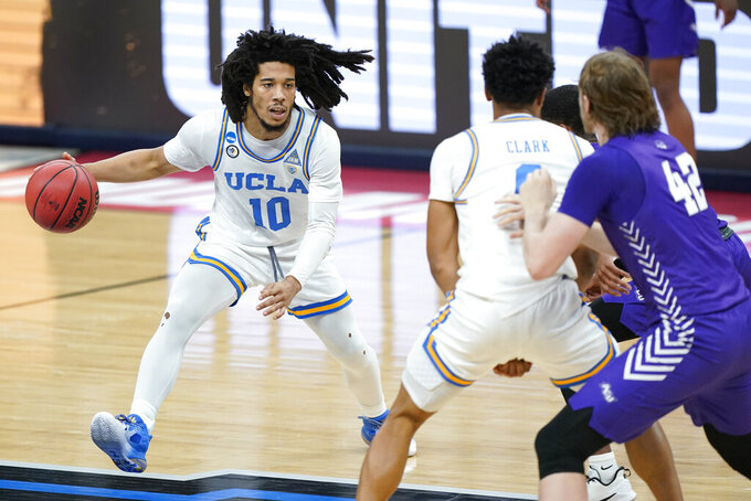 UCLA's Tyger Campbell (10) moves the ball against Abilene Christian during the first half of a college basketball game in the second round of the NCAA tournament at Bankers Life Fieldhouse in Indianapolis Monday, March 22, 2021. (AP Photo/Mark Humphrey)