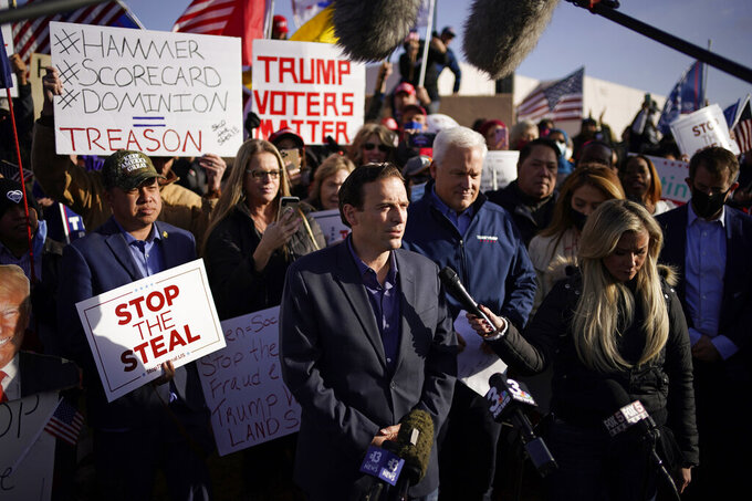 FILE - In this Nov. 8, 2020, file photo former Nevada Attorney General Adam Laxalt, middle speaking at microphone, and American Conservation Union Chairman Matt Schlapp speak during a news conference outside of the Clark County Election Department in North Las Vegas. The shadow of 2020 will likely figure into the Senate race in Nevada, where state legislators passed a law in May to send all voters mail-in ballots in future elections.  Laxalt referenced election integrity while former Trump cabinet member Ric Grenell and  Schlapp repeated their claims about voter fraud and Trump winning Nevada in the 2020 election without evidence. (AP Photo/John Locher, File)