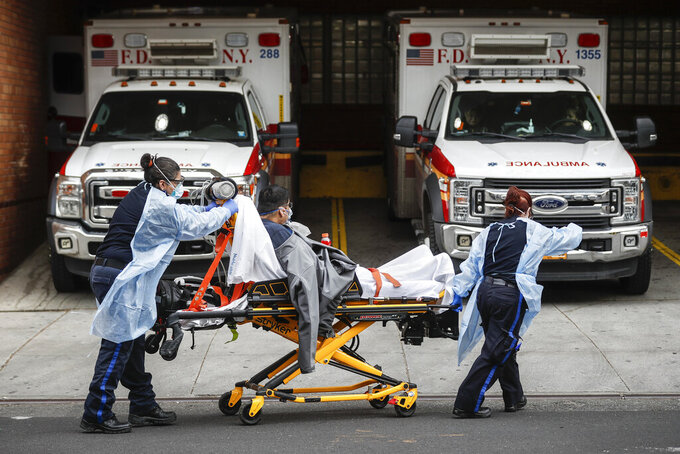FILE - In this April 7, 2020, file photo, patients are brought into Wyckoff Heights Medical Center by staff wearing personal protective gear due to COVID-19 concerns, in the Brooklyn borough of New York. The coronavirus has breathed fresh life into old conspiracy theories and inspired a mishmash of new ones, with a cast of villains that includes Bill Gates, 5G wireless technology, the United Nations and President Donald Trump's political foes. The baseless claims spreading on social media also feature videos taken outside hospitals treating COVID-19 patients. (AP Photo/John Minchillo, File)