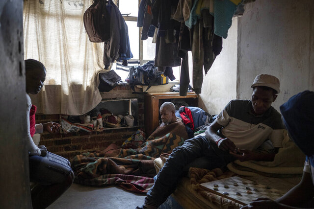 Bakair Zaina, a blind migrant from Mozambique, sits on the floor of his room he shares with two sons in Johannesburg, South Africa on April 14, 2020. A total of 23 families of blind and disabled foreign nationals living in the dilapidated building and earning a living by street begging have been hard hit by South Africa's lockdown as they are forced to remain indoors. (AP Photo/Bram Janssen)