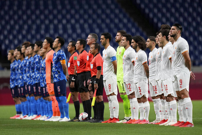 Players of Spain, right, and Japan, pose prior to their men's semifinal soccer match at the 2020 Summer Olympics, Tuesday, Aug. 3, 2021, in Saitama, Japon. (AP Photo/Silvia Izquierdo)