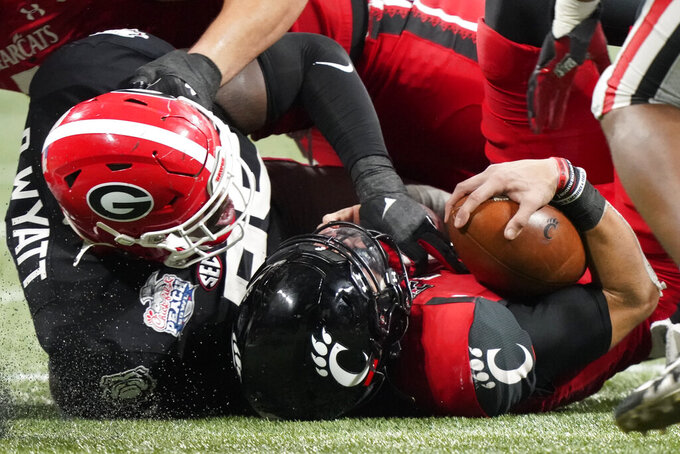 Georgia defensive lineman Devonte Wyatt (95) tackles Cincinnati quarterback Desmond Ridder (9) during the second half of the Peach Bowl NCAA college football game, Friday, Jan. 1, 2021, in Atlanta. (AP Photo/Brynn Anderson)