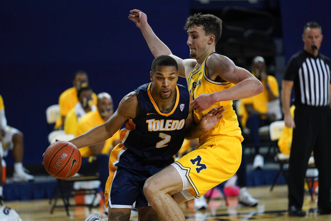 Toledo forward Setric Millner Jr. (2) drives on Michigan guard Franz Wagner (21) in the first half of an NCAA college basketball game in Ann Arbor, Mich., Wednesday, Dec. 9, 2020. (AP Photo/Paul Sancya)