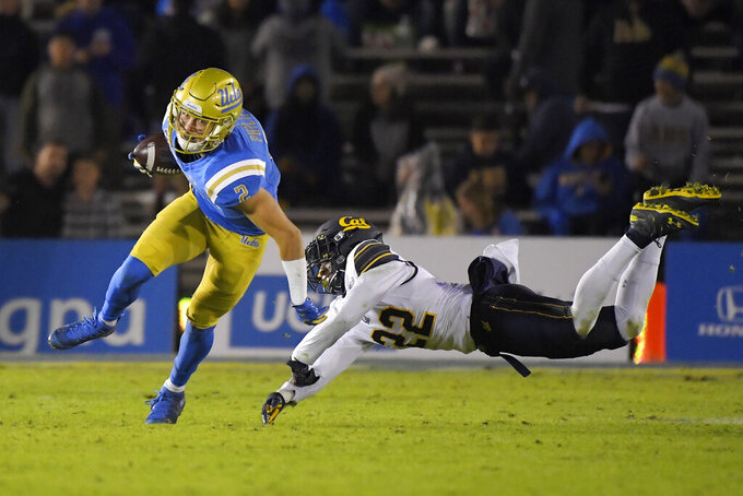 UCLA wide receiver Kyle Philips, left, breaks a tackle attempt by California cornerback Traveon Beck during the first half of an NCAA college football game Saturday, Nov. 30, 2019, in Pasadena, Calif. (AP Photo/Mark J. Terrill)