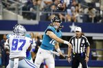 Dallas Cowboys defensive end Ron'Dell Carter (97) pressures as Jacksonville Jaguars quarterback Trevor Lawrence (16) throws a pass in the first half of a preseason NFL football game in Arlington, Texas, Sunday, Aug. 29, 2021. (AP Photo/Michael Ainsworth)