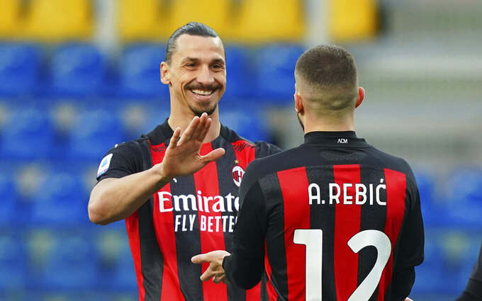 Milan's Ante Rebic celebrates after scoring his side's first goal, with teammate Zlatan Ibrahimovic, who gave him the assist, during the Italian Serie A soccer match between Parma and Milan at the Ennio Tardini stadium in Parma, Italy, Saturday, April 10, 2021.  (Spada/LaPresse via AP)