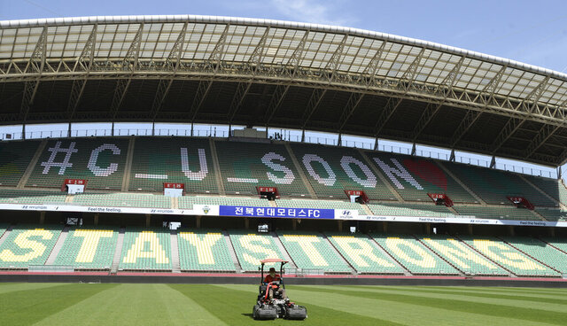 A worker trims the grass on the field at the Jeonju World Cup Stadium in Jeonju, South Korea, Thursday, May 7, 2020. South Korea's soccer league will kick off the season Friday, three days after the first pitch was thrown in baseball, in yet another sign that life in the country is starting to return to normal after strenuous efforts to contain the coronavirus.(Kim Orel/Newsis via AP)