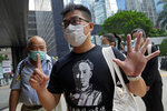 """Pro-democracy activist Raphael Wong gestures, signifying the """"Five demands - not one less,"""" outside a local court in Hong Kong Thursday, Aug. 19, 2021. A trial opens for seven prominent Hong Kong pro-democracy activists including Wong, in connection with an anti-government protest on Aug. 20, 2019. They are charged with """"incitement to knowingly take part in an unauthorized assembly."""" The trial is expected to last about a week. (AP Photo/Vincent Yu)"""