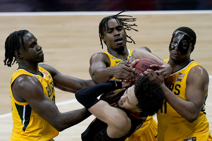 Oklahoma State's Cade Cunningham, front, battles for the ball with Baylor's Mark Vital, back right, Davion Mitchell, back center, and Jonathan Tchamwa Tchatchoua during the second half of an NCAA college basketball game in the semifinals of the Big 12 tournament in Kansas City, Mo., Friday, March 12, 2021. (AP Photo/Charlie Riedel)