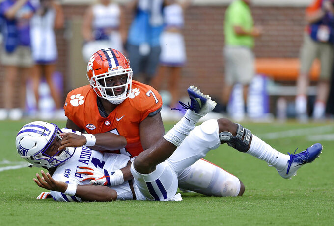 Furman quarterback Darren Grainger knocked down by Clemson's Austin Bryant after scrambling out of the pocket during the first half of an NCAA college football game Saturday, Sept. 1, 2018, in Clemson, S.C. (AP Photo/Richard Shiro)