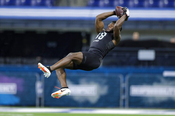 Auburn defensive back Noah Igbinoghene runs a drill at the NFL football scouting combine in Indianapolis, Sunday, March 1, 2020. (AP Photo/Michael Conroy)