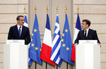 French President Emmanuel Macron, right, and Greek Prime Minister Kyriakos Mitsotakis attend a joint press conference at the Elysee Palace in Paris, Wednesday Jan. 29, 2020. (Benoit Tessier/Pool via AP)
