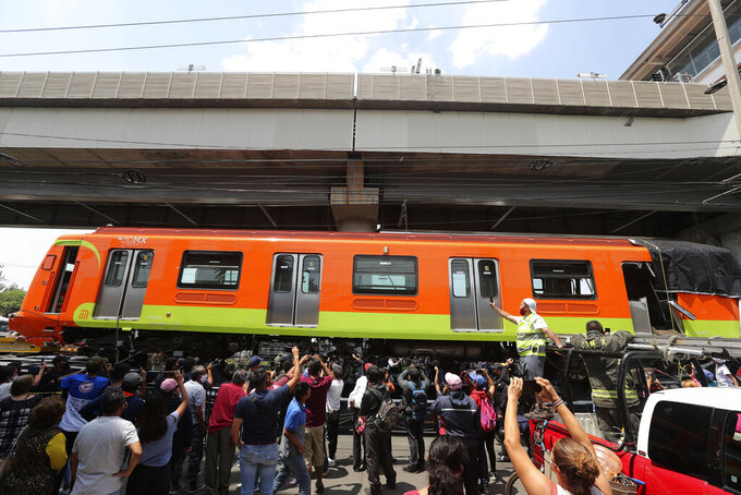 A damaged subway car is removed after it was lowered from a collapsed elevated section of the metro, in Mexico City, Tuesday, May 4, 2021. The elevated section of the metro collapsed late Monday, killing at least 23 people and injuring at least 79, city officials said. (AP Photo/Marco Ugarte)
