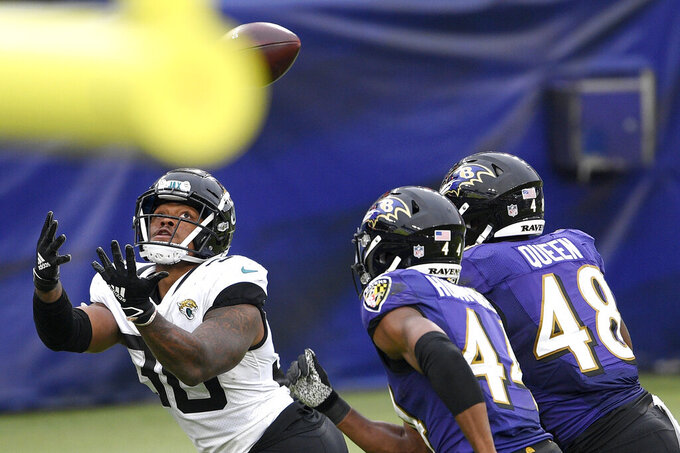 Jacksonville Jaguars running back James Robinson, left, watches the ball before making a touchdown catch on a pass from quarterback Gardner Minshew II (not shown) as Baltimore Ravens cornerback Marlon Humphrey (44) and linebacker Patrick Queen (48) defend during the second half of an NFL football game, Sunday, Dec. 20, 2020, in Baltimore. (AP Photo/Nick Wass)