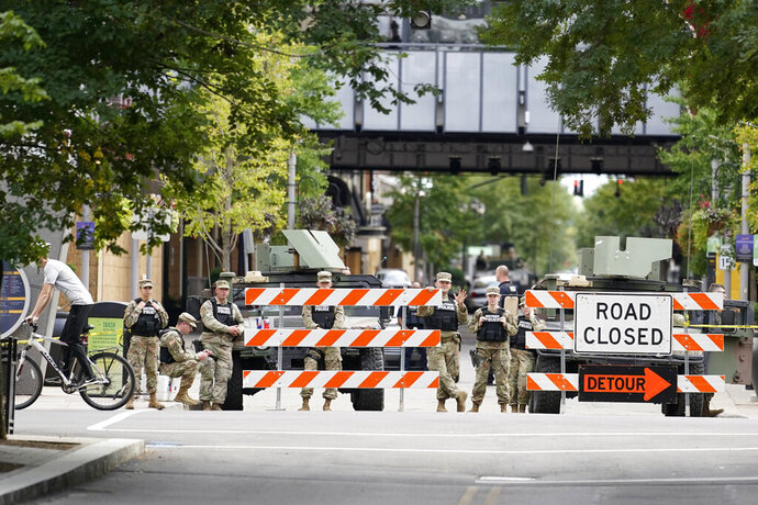 Police stand near a barricade, Friday, Sept. 25, 2020, in Louisville. Breonna Taylor's family demanded Friday that Kentucky authorities release all body camera footage, police files and the transcripts of the grand jury hearings that led to no charges against police officers who killed the Black woman during a March drug raid at her apartment. (AP Photo/Darron Cummings)