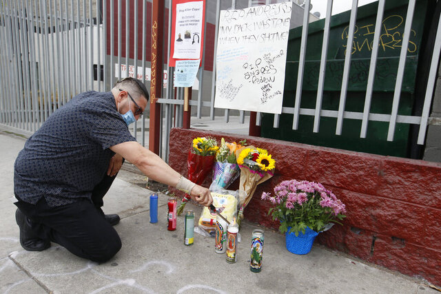 Family member Noe Abarca lights candles, for nephew, victim Andres Guardado, 18, who was fatally shot by a Los Angeles County sheriff's deputy in Gardena, Calif., Friday, June 19, 2020. Los Angeles County sheriff's detectives on Friday were investigating a deputy's fatal shooting of a young man who reportedly was working as a security guard at a local auto body shop. The shooting occurred just before 6 p.m. Thursday. Sheriff's Lt. Charles Calderaro told reporters the man was not wearing a security guard uniform when deputies saw him and they did not have information regarding his occupation. (AP Photo/Damian Dovarganes)