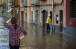 A firefighter speaks with a resident inside his house, during flooding following a storm in Girona, Spain, on Thursday, Jan. 23, 2020. At least 11 have died and five people remained missing on Thursday following a calamitous storm that has caused rivers to overflow and sea waters to inundate vast agricultural areas in eastern Spain. (AP Photo/Emilio Morenatti)