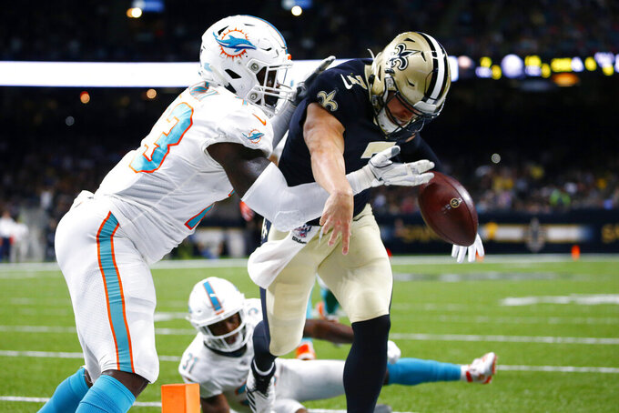 Miami Dolphins defensive end Dewayne Hendrix (73) knocks the ball out of the hands of New Orleans Saints quarterback Taysom Hill (7) just short of the end zone in the second half of an NFL preseason football game in New Orleans, Thursday, Aug. 29, 2019. (AP Photo/Butch Dill)