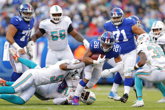 New York Giants running back Saquon Barkley (26) runs with the ball as members of the Miami Dolphins try to stop him in the second half of an NFL football game, Sunday, Dec. 15, 2019, in East Rutherford, N.J. (AP Photo/Adam Hunger)