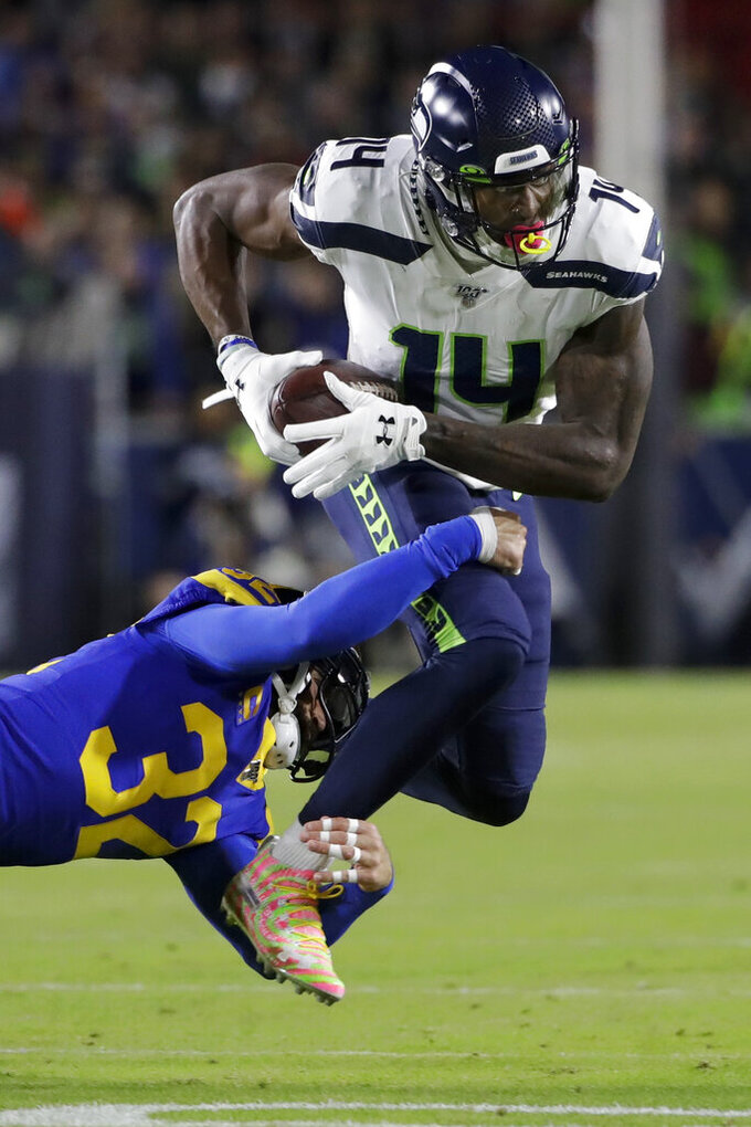 Seattle Seahawks wide receiver D.K. Metcalf is tackled by Los Angeles Rams free safety Eric Weddle during the first half of an NFL football game Sunday, Dec. 8, 2019, in Los Angeles. (AP Photo/Marcio Jose Sanchez)