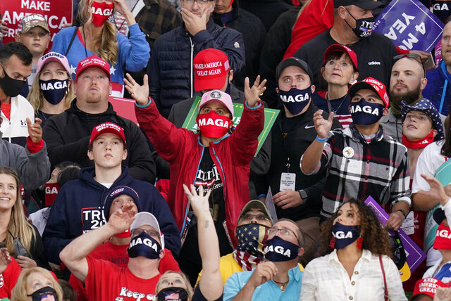 A supporter catches a hat before President Donald Trump's arrival an airport rally, Wednesday, Oct. 14, 2020, in Des Moines, Iowa. (AP Photo/Charlie Neibergall)