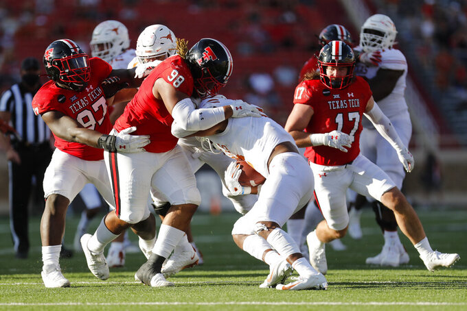 Texas Tech defensive lineman Nick McCann tackles Texas running back Roschon Johnson during the second half of an NCAA college football game against Texas Tech, Saturday Sept. 26, 2020, in Lubbock, Texas. (AP Photo/Mark Rogers)