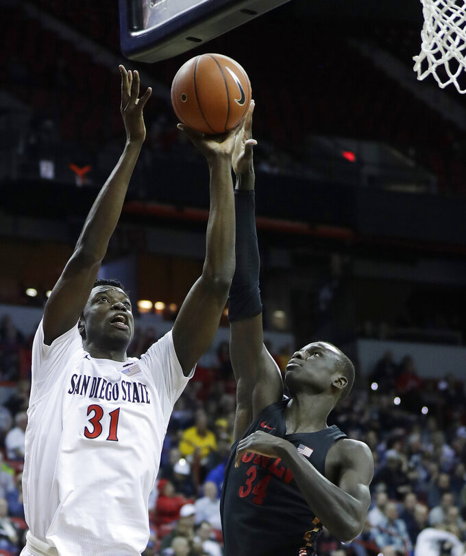 San Diego State's Nathan Mensah (31) shoots as UNLV's Cheikh Mbacke Diong (34) defends during the first half of an NCAA college basketball game in the Mountain West Conference men's tournament Thursday, March 14, 2019, in Las Vegas. (AP Photo/Isaac Brekken)