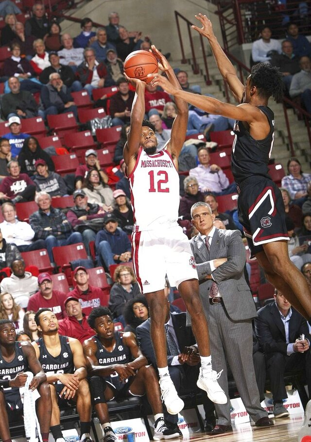 Carl Pierre, left, of Massachusetts launches up a 3-pointer from the corner over South Carolina's AJ Lawson during the first half of an NCAA college basketball game against Massachusetts Wednesday, Dec. 4, 2019, in Amherst, Mass. (J. Anthony Roberts/The Republican via AP)