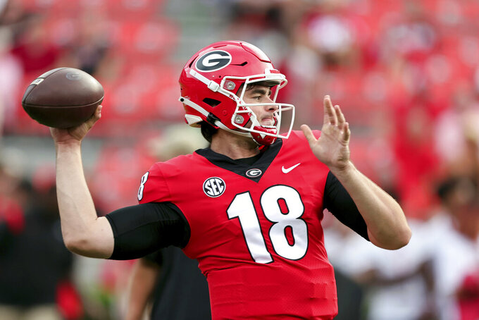 Georgia quarterback JT Daniels (18) warms up for the team's NCAA college football game against South Carolina on Saturday, Sept. 18, 2021, in Athens, Ga. (AP Photo/Butch Dill)