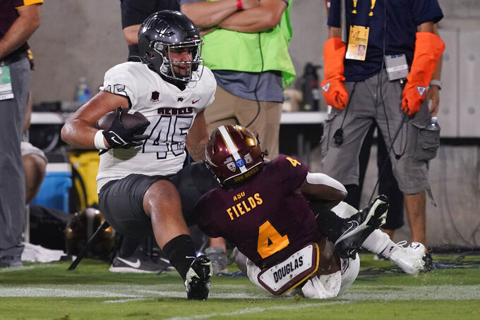 Arizona State defensive back Evan Fields (4) tackles UNLV tight end Giovanni Fauolo Sr. (45) during the second half of an NCAA college football game, Saturday, Sept. 11, 2021, in Tempe, Ariz. (AP Photo/Matt York)