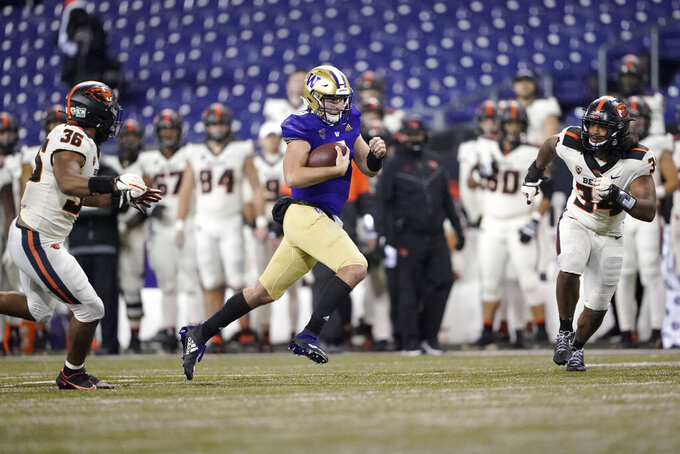 Washington quarterback Dylan Morris keeps the ball as Oregon State's Omar Speights, left, and Avery Roberts, right, close in during the second half of an NCAA college football game, Saturday, Nov. 14, 2020, in Seattle. Washington won 27-21. (AP Photo/Ted S. Warren)