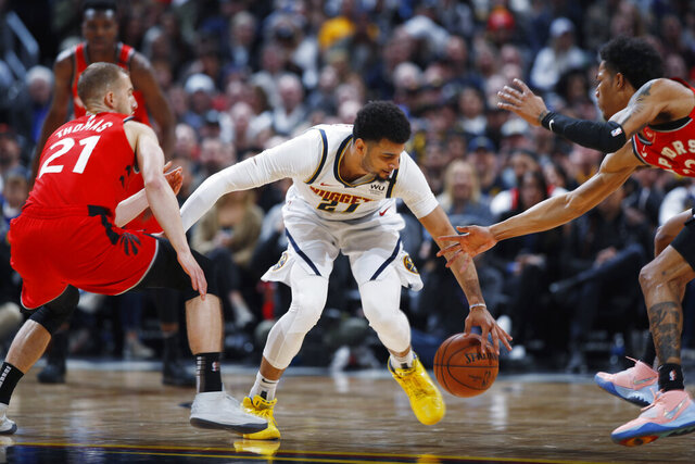 Denver Nuggets guard Jamal Murray, center, recovers the ball between Toronto Raptors guard Matt Thomas, left, and forward Patrick McCaw in the first half of an NBA basketball game Sunday, March 1, 2020. (AP Photo/David Zalubowski)