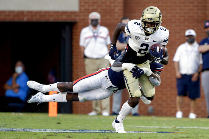 Akron running back Anthony Williams Jr. (2) is tack;ed from behind by Auburn linebacker Owen Pappoe during the first half of an NCAA college football game Saturday, Sept. 4, 2021, in Auburn, Ala. (AP Photo/Butch Dill)