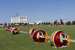 Helmets are lined up along the practice field as players begin drills during the first day of the Washington Redskins NFL football training camp in Richmond, Va., Thursday, July 25, 2019. (AP Photo/Steve Helber)