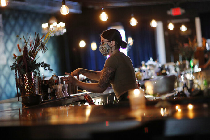 FILE - In this July 10, 2020, file photo, Alanna McDonnell mixes drinks at Velveteen Rabbit, a cocktail bar in the Las Vegas Arts District in Las Vegas. Bars in and around Las Vegas can reopen after this weekend with limited capacity, distance between customers and facial coverings all around, officials announced Thursday, Sept. 17, 2020. (AP Photo/John Locher, File)
