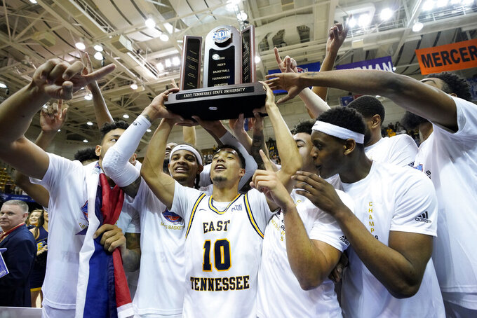 East Tennessee State guard Patrick Good (10) and teammates raise their NCAA men's basketball Southern Conference championship trophy after defeating Wofford, Monday, March 9, 2020, in Asheville, N.C. (AP Photo/Kathy Kmonicek)