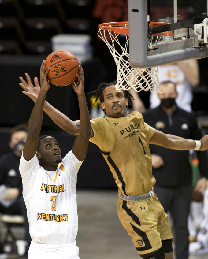 Northern Kentucky guard Marques Warrick (3) is fouled by Purdue-Fort Wayne guard Jarred Godfrey (1) while attempting to dunk during the second half of an NCAA college basketball game Friday, Jan. 1, 2021, in Highland Heights, Ky. (Albert Cesare/The Cincinnati Enquirer via AP)