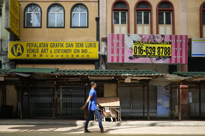 A man wearing face mask walks by closed shops at China town in Kuala Lumpur, Malaysia, Monday, June 28, 2021. Prime Minister Muhyiddin Yassin on Sunday said the lockdown won't be eased unless daily new cases fall below 4,000, the vaccination rate reaches 10% and demand is reduced for intensive care in hospitals.(AP Photo/Vincent Thian)