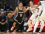 Atlanta Hawks guard Trae Young (11) is defended by Milwaukee Bucks guard Donte DiVincenzo (0) in the first half of an NBA basketball game, Wednesday, Nov. 20, 2019, in Atlanta. (AP Photo/Brett Davis)