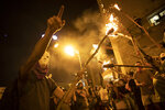 Protesters light torches during a protest against Israel's Prime Minister Benjamin Netanyahu outside his residence in Jerusalem, Saturday, Aug 1, 2020. Protesters demanded that the embattled Israeli leader to resign as he faces a trial on corruption charges and grapples with a deepening coronavirus crisis. (AP Photo/Oded Balilty)