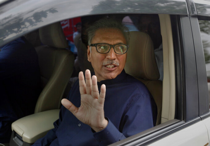 FILE - In this Aug. 27, 2018 file photo, Arif Alvi, then a lawmaker from Imran Khan's Tehreek-e-Insaf ruling party waves to media after filing his nomination papers in the presidential election, in Islamabad, Pakistan. President Arif Alvi took to Twitter Monday, March, 29, 2021 posting that he has tested positive for the coronavirus after having his first dose of the vaccine. The latest development comes nine days after the country's prime minister Imran Khan tested positive for coronavirus. (AP Photo/Anjum Naveed, File)