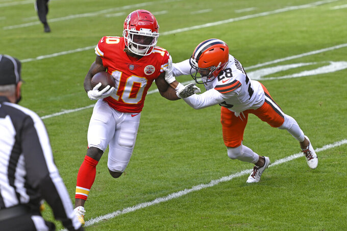 Kansas City Chiefs wide receiver Tyreek Hill (10) runs from Cleveland Browns cornerback Kevin Johnson (28) during the first half of an NFL divisional round football game, Sunday, Jan. 17, 2021, in Kansas City. (AP Photo/Reed Hoffmann)