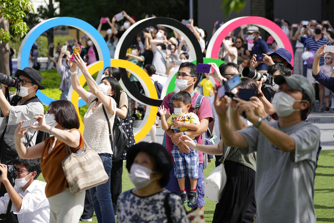 People gather near the National Stadium in Tokyo as Blue Impulse of the Japan Air Self-Defense Force practice ahead of the 2020 Summer Paralympics, Sunday, Aug. 22, 2021.(Ryosuke UematsuKyodo News via AP)