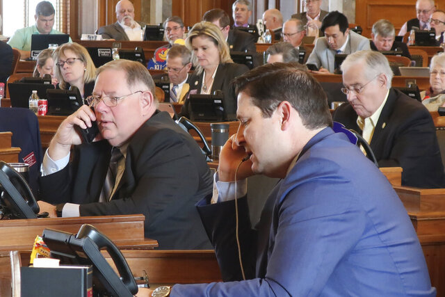 Kansas House Majority Leader Dan Hawkins, center left, R-Wichita, and House Speaker Ron Ryckman Jr., center right, R-Olathe, work the phones during a House vote on a proposed amendment to the state constitution on abortion, Friday, Feb. 7, 2020, at the Statehouse in Topeka, Kansas. Hawkins and Ryckman were trying to round up the final votes needed to pass the proposed amendment, which overturns a Kansas Supreme Court decision declaring access to abortion a