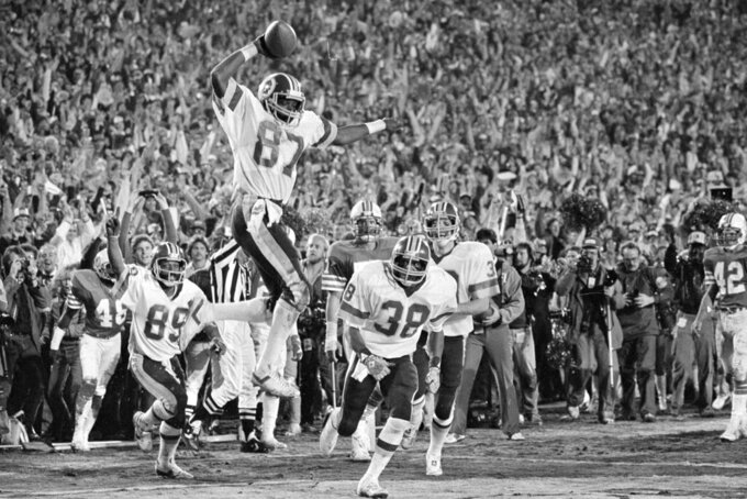 FILE - In this Jan. 30, 1983, file photo, Washington Redskins receiver Charlie Brown (87) gets ready to spike the ball after he scored a fourth quarter touchdown against the Miami Dolphins in Super Bowl XVII in Pasadena, Calif. Coming over to congratulate Brown are teammates Alvin Garrett (89) and Clarence Harmon (38). The  Redskins won 27-17. (AP Photo/File)