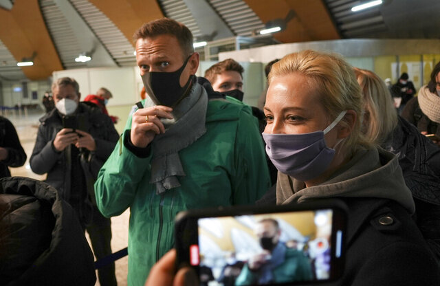 Alexei Navalny and his wife Yuliastand in line at the passport control after arriving at Sheremetyevo airport, outside Moscow, Russia, Sunday, Jan. 17, 2021. Russia's prison service says opposition leader Alexei Navalny has been detained at a Moscow airport after returning from Germany. (AP Photo/Mstyslav Chernov)