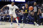 Marquette's Markus Howard (0) drives against Xavier Naji Marshall (13) during the first half of an NCAA college basketball game Wednesday, Jan. 29, 2020, in Cincinnati. (AP Photo/John Minchillo)