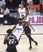 Orlando Magic forward Jonathan Isaac shoots next to Sacramento Kings center Richaun Holmes (22) during an NBA basketball game Sunday, Aug. 2, 2020, in Lake Buena Vista, Fla. (Charles King/Orlando Sentinel via AP)